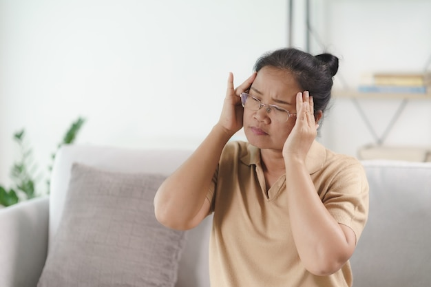 Épuisé, fatigué, déprimé, stressé, mûr, réfléchi, femme âgée souffrant de maux de tête, de maladies du cerveau, de problèmes mentaux, d'alzheimer concept.