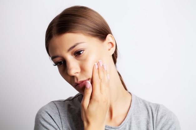 Épuisé jeune femme souffrant de maux de dents sévères