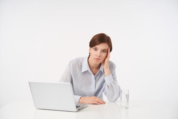 Épuisé jeune jolie femme brune aux cheveux courts avec un maquillage naturel en se penchant la tête sur la main levée et à la fatigue, isolé sur blanc