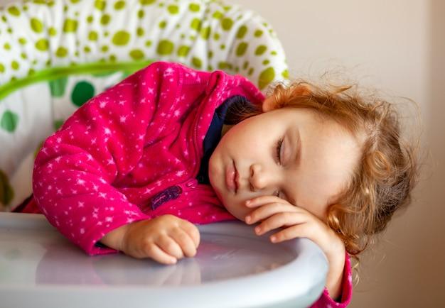 Épuisé petite fille endormie dans la chaise haute