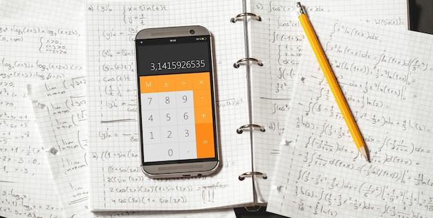 Équations mathématiques écrites dans un cahier. application de calculatrice.