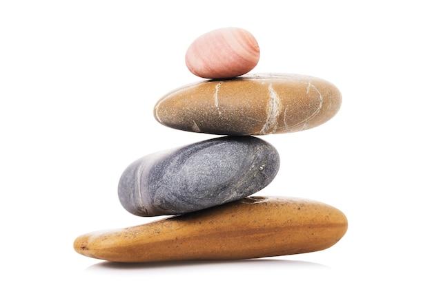 L'équilibrage des cailloux isolés sur des pierres de mer de surface blanche en équilibre