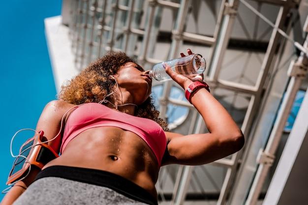 Équilibre du ph. faible angle d'une belle jeune femme en forme de boire de l'eau douce