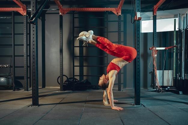 Équilibré. jeune femme caucasienne musclée pratiquant dans la salle de gym. modèle féminin athlétique faisant des exercices de force, entraînant le bas et le haut du corps, des étirements. bien-être, mode de vie sain, musculation.