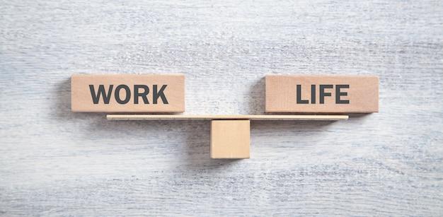 Équilibre travail-vie sur fond de bois blanc.