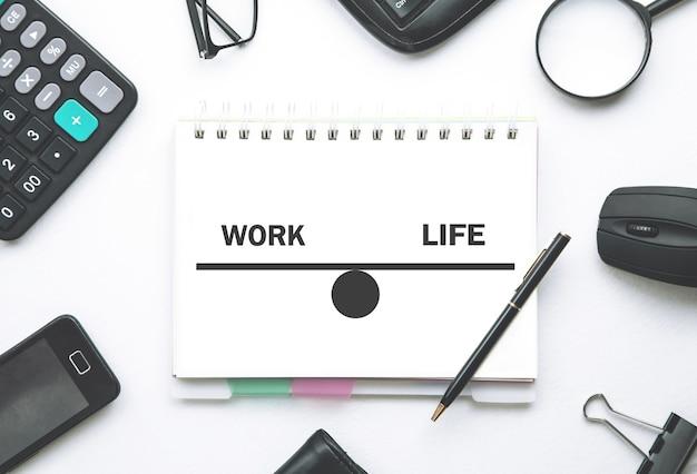 Équilibre travail-vie personnelle sur le bloc-notes avec un objet métier
