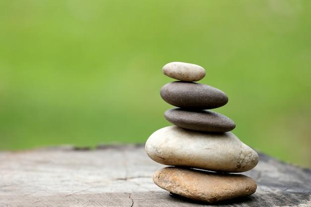 Équilibrer les pierres empilées en pyramide sur le fond vert tendre.