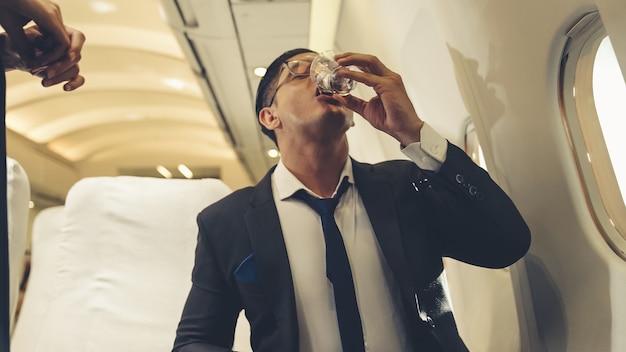 L'équipage de cabine sert de l'eau au passager en avion
