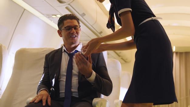 L'équipage de cabine sert de l'eau au passager dans l'avion. concept de transport aérien et de tourisme.