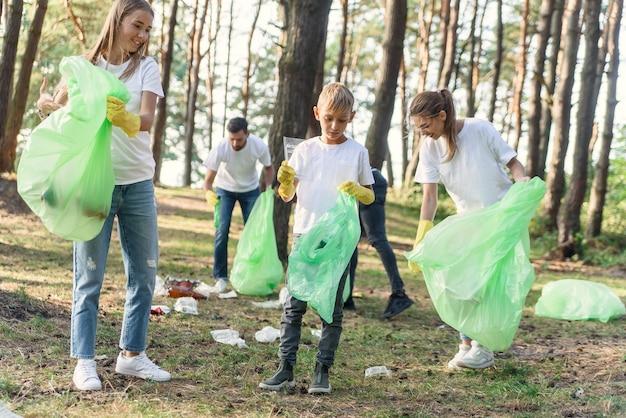 Équipe active de naturalistes internationaux en t-shirs blancs ramassant des déchets dans des emballages en plastique dans la forêt.