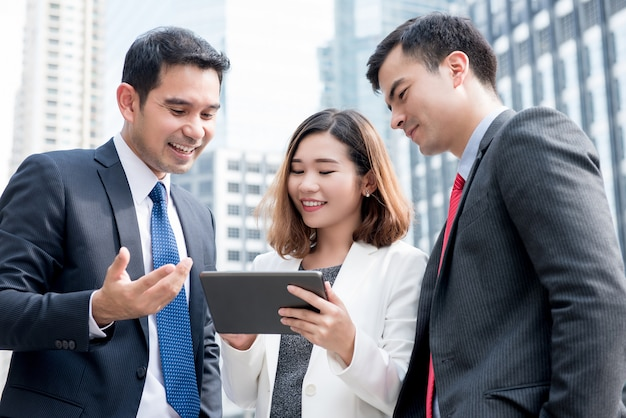 Équipe des activités asiatiques discuter et partager des travaux en ligne sur une tablette à l'extérieur