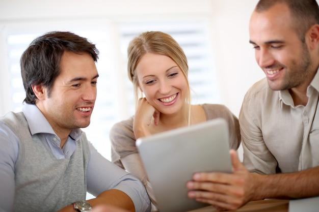 Équipe des activités au bureau travaillant sur une tablette