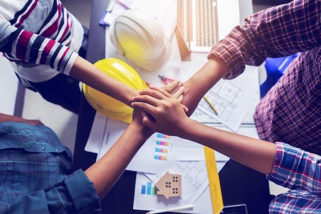 Équipe des activités debout les mains ensemble au bureau