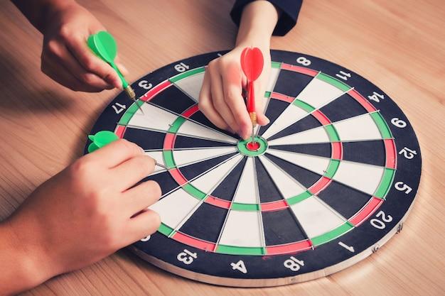Équipe des activités pointant vers un jeu de fléchettes visant le centre des affaires