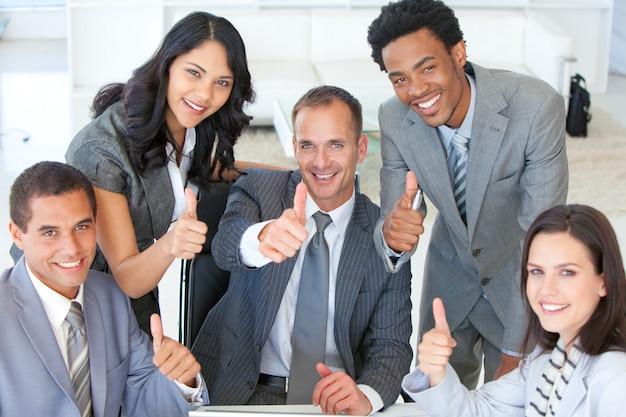 Équipe des activités avec les pouces au bureau