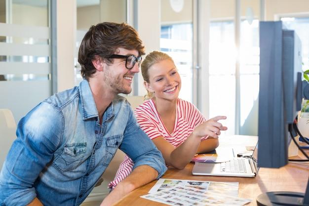 Équipe des activités / travail souriant avec ordinateur