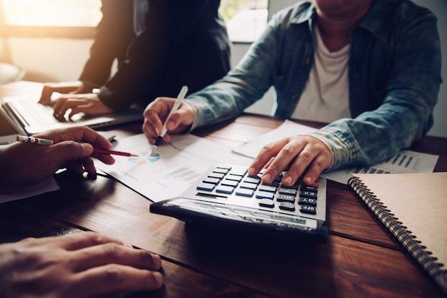 Équipe des activités travaillant avec un ordinateur portable et une calculatrice dans les bureaux open space. rapport de réunion en cours