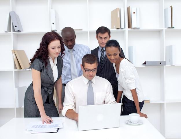 Équipe des activités utilisant un ordinateur portable ensemble