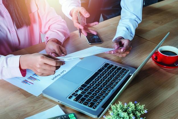 Équipe des affaires analysant les graphiques et les graphiques des revenus avec un ordinateur portable moderne.