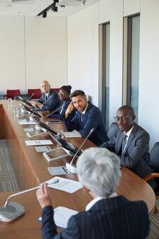 Équipe des affaires assis à la table et à l'écoute de la femme d'affaires à la conférence