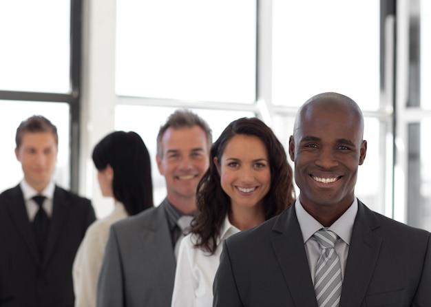 Équipe d'affaires de cinq personnes regardant la caméra et souriant