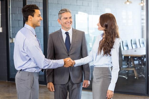 Équipe d'affaires debout ensemble et interagissant dans le bureau