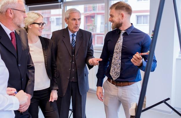 Équipe d'affaires dynamique discutant autour d'un tableau blanc dans une salle de réunion