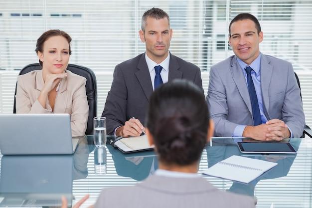 Équipe d'affaires écoutant le demandeur en entrevue