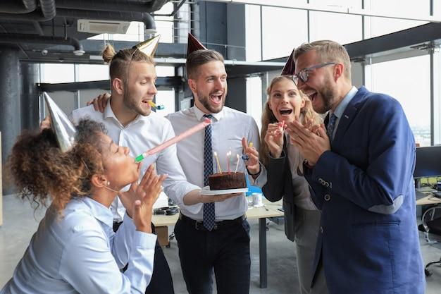 Une équipe d'affaires heureuse avec un gâteau d'anniversaire salue un collègue lors d'une fête de bureau.