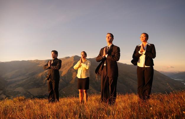 Équipe des affaires méditant sur le sommet des montagnes.