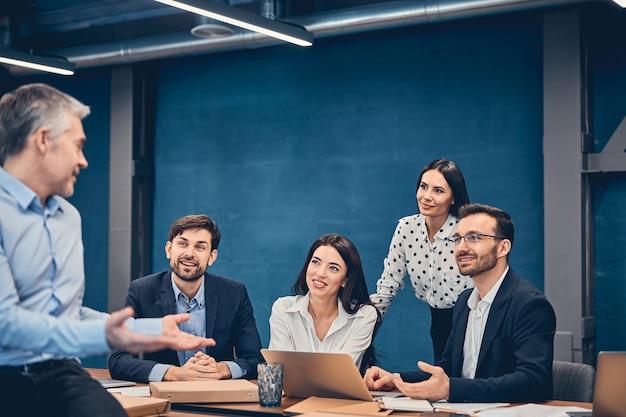 Équipe d'affaires en réunion de salle de réunion dans un grand immeuble de bureaux moderne