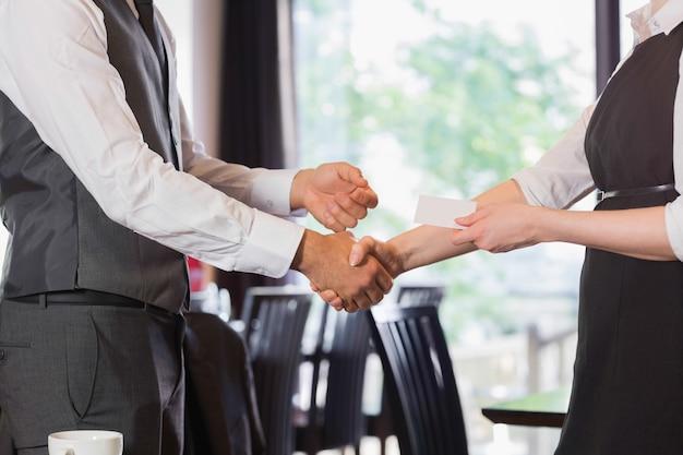 Équipe des affaires se serrant la main et échanger la carte