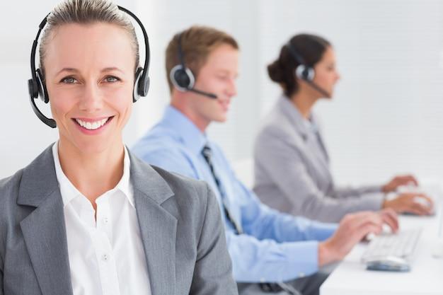 Équipe d'affaires travaillant sur des ordinateurs et portant des casques d'écoute