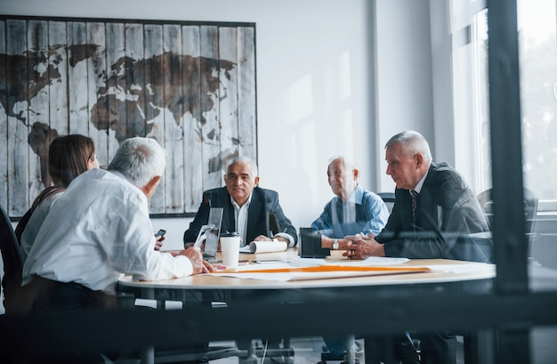 Une équipe âgée d'architectes d'affaires âgés se réunit au bureau et travaille avec une jeune femme.