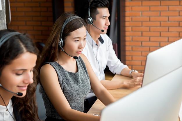 Équipe d'agents du service clientèle multi-ethnique en télémarketing