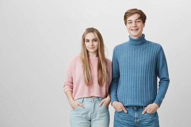 Équipe amicale, collaboration et coopération. heureux couple souriant, portant des vêtements tricotés et des jeans
