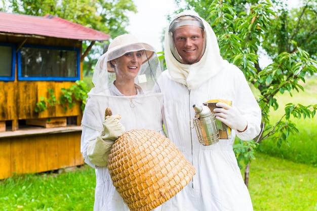 Équipe d'apiculteurs travaillant à l'extérieur avec fumeur et ruche