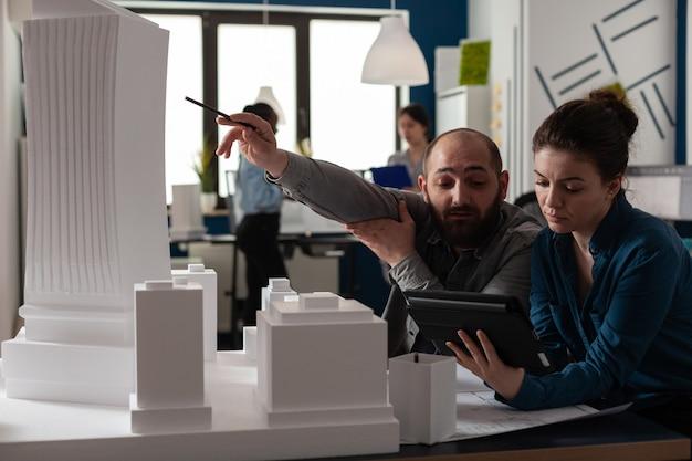 Une équipe d'architectes en construction travaille sur une tablette au bureau