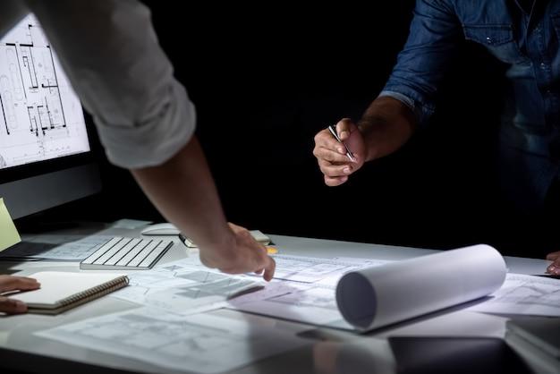 Équipe d'architectes discutant du papier modèle au bureau