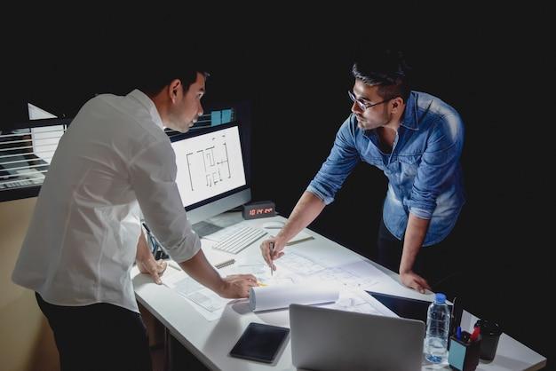 Équipe d'architectes discutant de projet la nuit