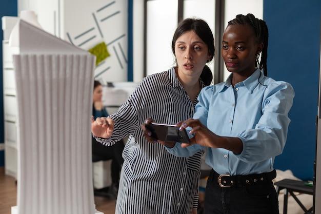 Équipe d'architectes multiethniques travaillant sur smartphone