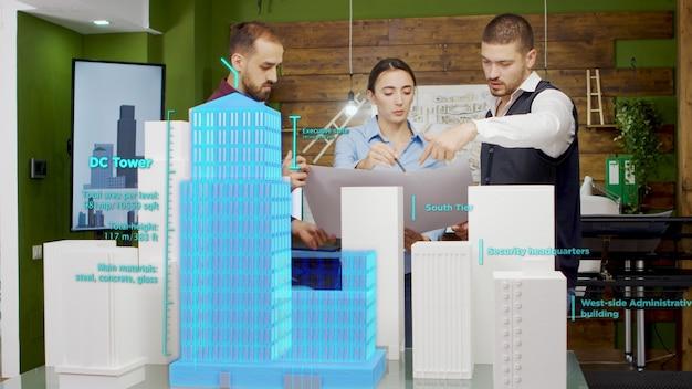 Équipe d'architectes travaillant sur les gratte-ciel de la ville à l'aide d'hologrammes de réalité augmentée. hologrammes couvrant des modèles de bâtiments 3d