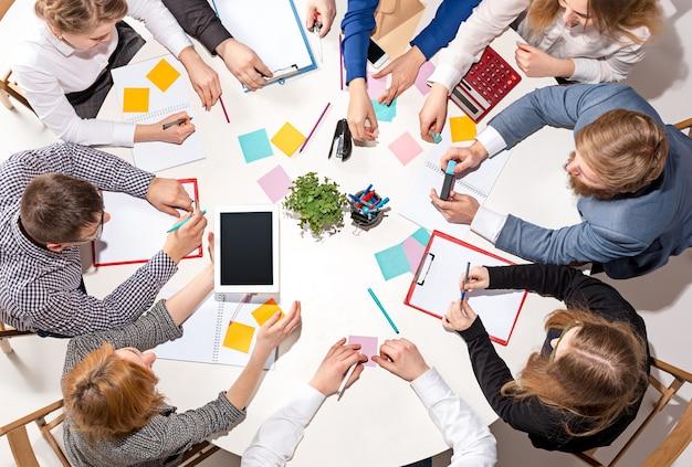Équipe assise derrière le bureau, vérifiant les rapports, parlant. vue de dessus.