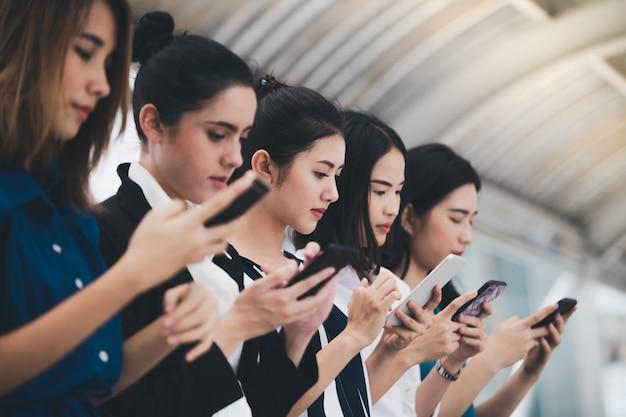 Équipe attrayante de femmes d'affaires asiatiques jouant smartphone