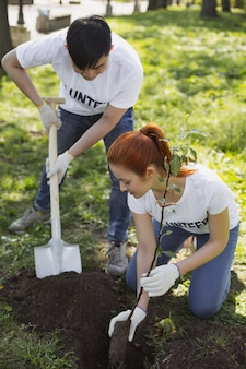 Équipe de bénévoles. agréable deux volontaires utilisant une pelle et regardant vers le bas
