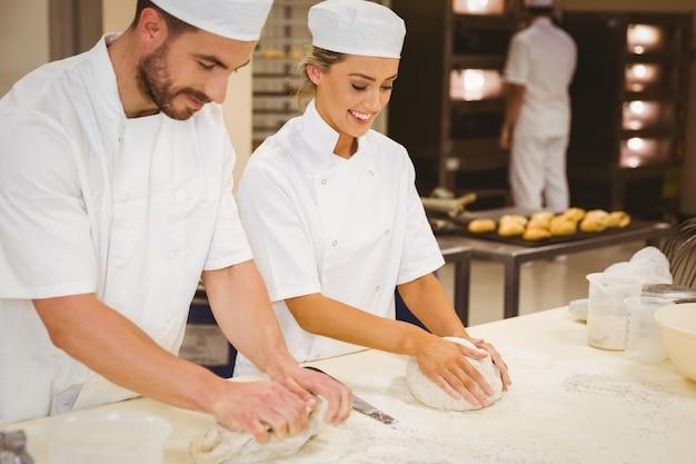 Équipe de boulangers pétrir la pâte