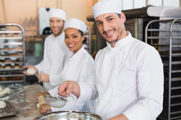 Équipe de boulangers souriant à la caméra