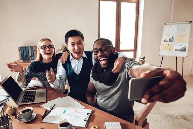 Une équipe de bureau confiante et réussie prend selfie.