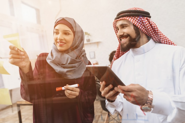 Équipe de bureau des musulmans heureux écrivant sur la planche de verre