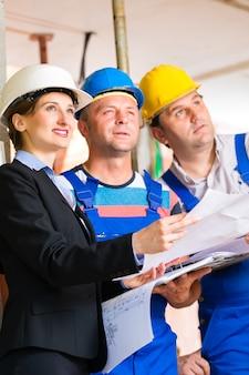 L'équipe de chantier ou l'architecte et le constructeur ou le travailleur avec des casques contrôlant ou discutant du plan ou du plan directeur